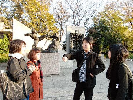 [写真]学外研究/屋外で語り合う学生