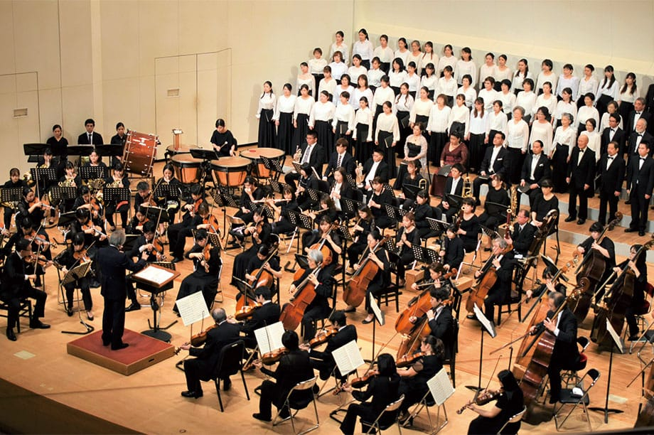 [写真]金管楽器を抱えて音楽棟前を歩く女子学生