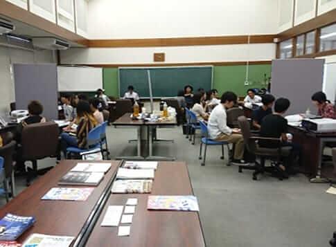 [写真]教室内に設けられたブースで説明をする企業担当者と、聞き入る学生