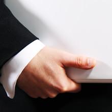 [写真]企業マンがパソコンを抱えているイメージ