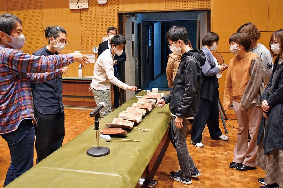 [写真]沖縄民族踊りを踊る女性たちとフィールドワーク中の学生