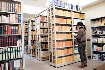 [写真]研究科書庫で本を閲覧する女子学生
