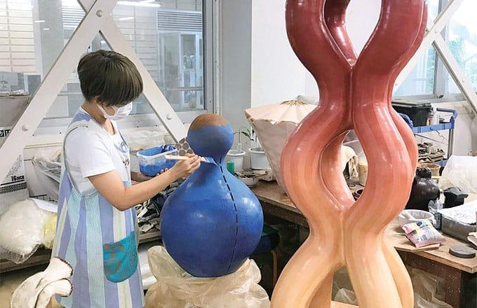 [写真]芸術文化学研究科のワークショップで民族楽器について解説している外国人男性と女子学生