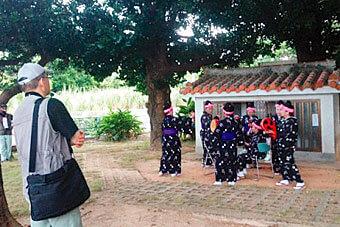 [写真]沖縄で複数の女性が踊る民族踊りをリサーチしている男子学生