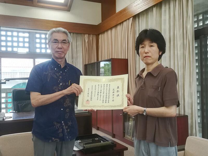 [写真]表彰状を手にする高瀬教授と比嘉学長