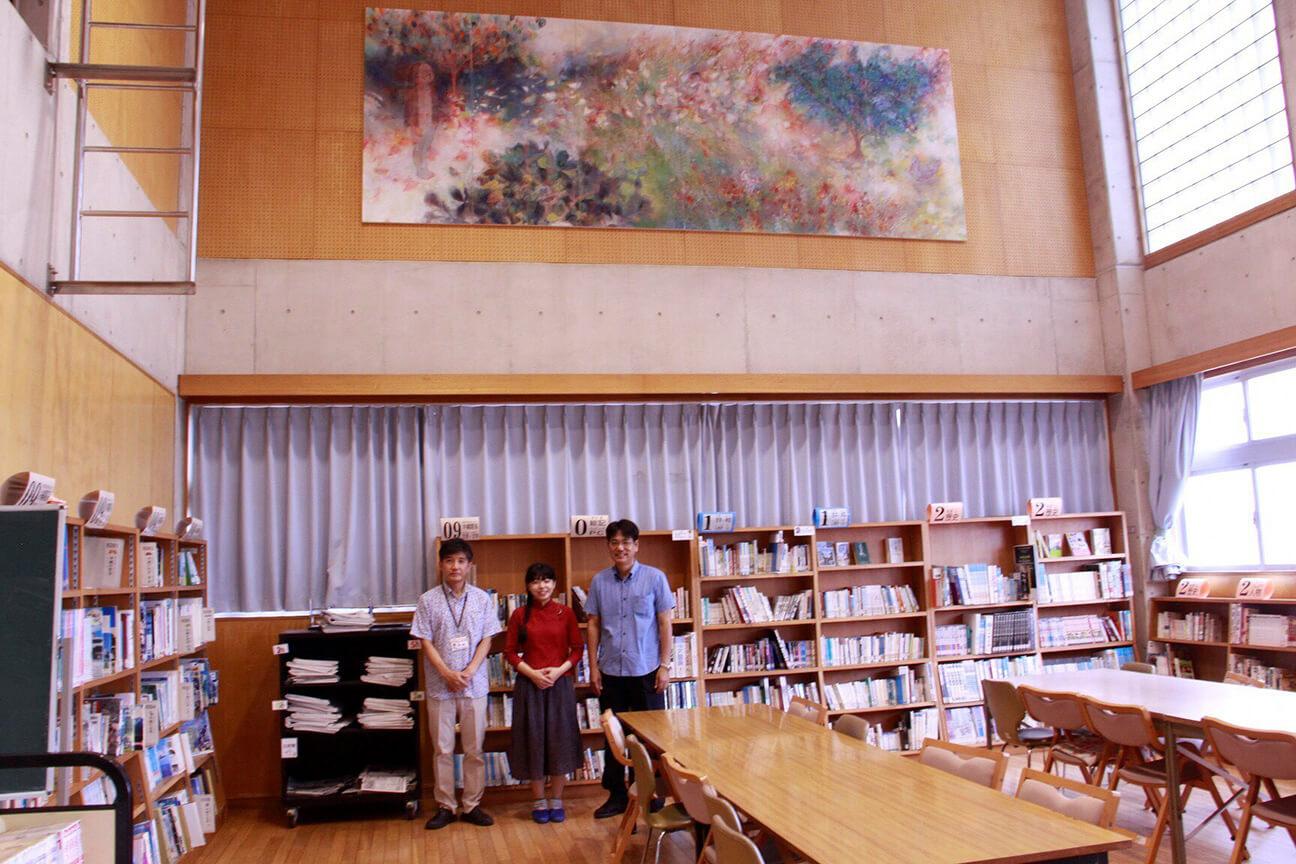 [写真]設置された作品の下、左から望月教頭、小林さん、松田校長