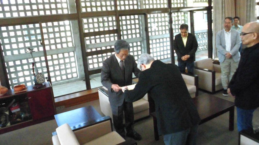 [写真]授与書を受け取る安里進名誉教授