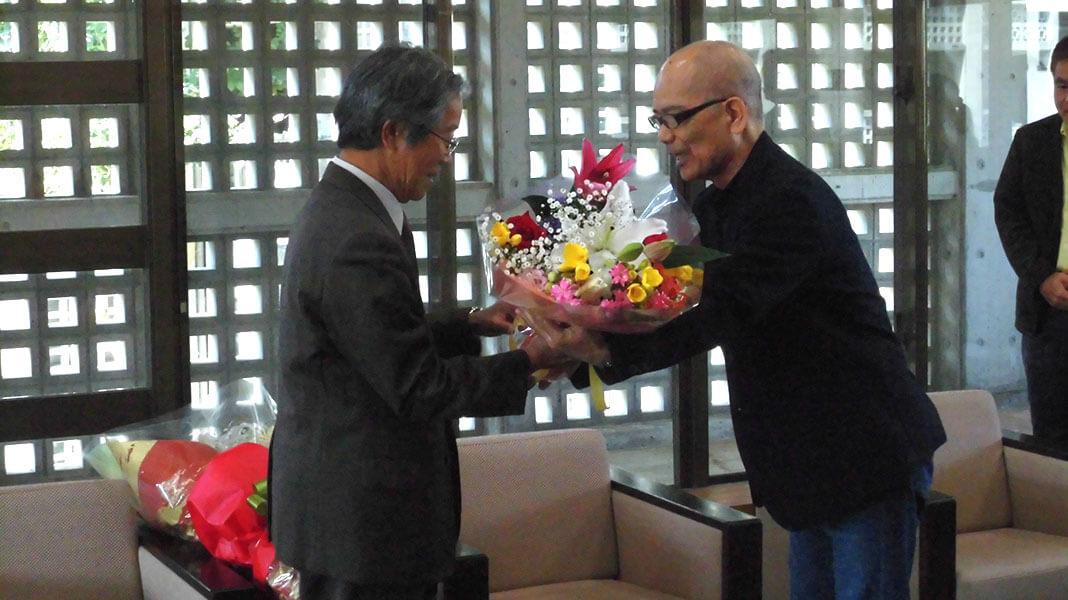 [写真]花束を贈呈される安里進名誉教授