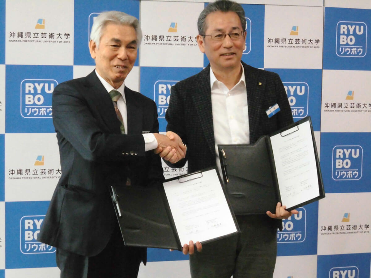[写真]握手する比嘉学長と糸数剛一代表取締役社長