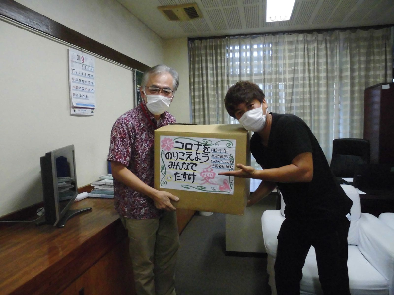 [写真]寄贈品を手にする株式会社千寿ご担当者様と本学事務局長